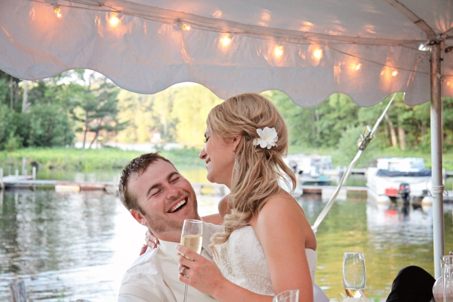 Bride and Groom share some laughs during their lakeside wedding reception-DMP